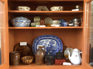 Kitchen cupbaord exhibit showing pottery and household items over time