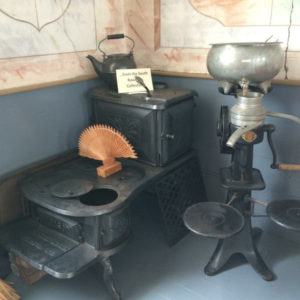 Historic kitchen display with stove, kettle and other items